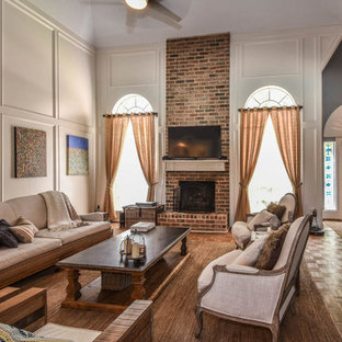 Example of a large transitional open concept medium tone wood floor family room design in Houston with gray walls, a standard fireplace, a brick fireplace and a wall-mounted tv