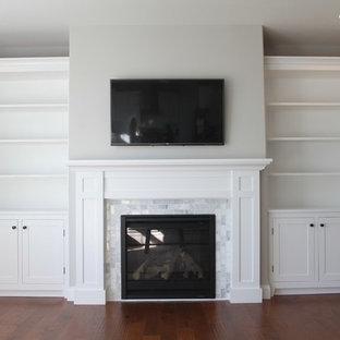 Réalisation d'une grande salle de séjour craftsman fermée avec un mur blanc, un sol en bois clair, une cheminée standard, un manteau de cheminée en pierre et un téléviseur encastré.