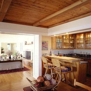 サンタバーバラのビーチスタイルのおしゃれなファミリールーム (白い壁、無垢フローリング、コーナー設置型暖炉、レンガの暖炉まわり、壁掛け型テレビ) の写真
