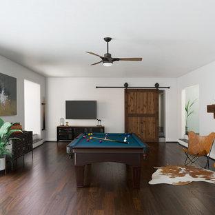 他の地域のコンテンポラリースタイルのおしゃれなファミリールーム (ゲームルーム、白い壁、濃色無垢フローリング、壁掛け型テレビ、茶色い床) の写真