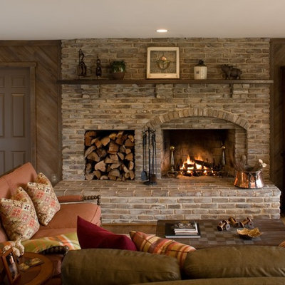 Example of a classic family room design in DC Metro with brown walls, a standard fireplace and a brick fireplace