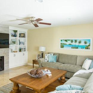 Modelo de sala de estar abierta, marinera, de tamaño medio, con paredes beige, suelo de travertino, chimenea tradicional, televisor colgado en la pared, suelo beige y marco de chimenea de madera