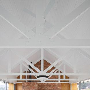 Ejemplo de sala de estar abierta, de estilo de casa de campo, de tamaño medio, con paredes beige, suelo de cemento, chimenea tradicional, marco de chimenea de metal, televisor colgado en la pared y suelo gris