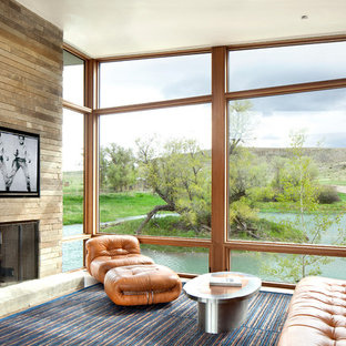 Example of a minimalist open concept family room design in Los Angeles with a standard fireplace, a stone fireplace and a wall-mounted tv