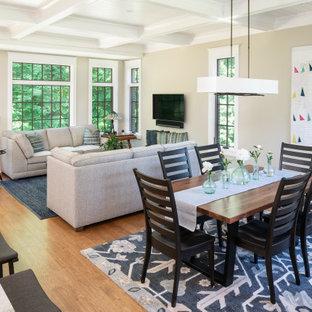 Imagen de sala de estar abierta, tradicional, grande, sin chimenea, con paredes beige, suelo de madera en tonos medios, televisor colgado en la pared y suelo marrón