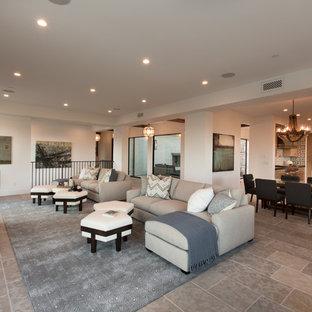 Idee per un ampio soggiorno tradizionale aperto con pareti bianche, pavimento in pietra calcarea, camino classico, cornice del camino in cemento e TV a parete