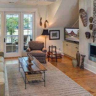 Imagen de sala de estar con biblioteca cerrada, campestre, pequeña, con paredes blancas, suelo de madera clara, chimenea tradicional, marco de chimenea de metal y televisor independiente