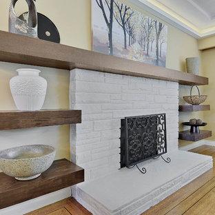 バンクーバーの中サイズのコンテンポラリースタイルのおしゃれなファミリールーム (ベージュの壁、淡色無垢フローリング、標準型暖炉、レンガの暖炉まわり、テレビなし、茶色い床) の写真
