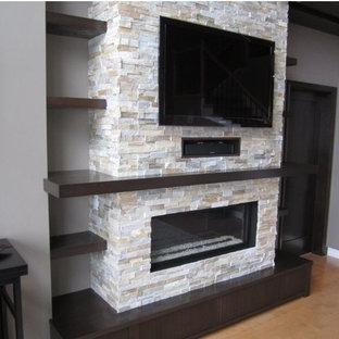Inspiration pour une salle de séjour traditionnelle avec une cheminée ribbon, un manteau de cheminée en pierre et un téléviseur fixé au mur.