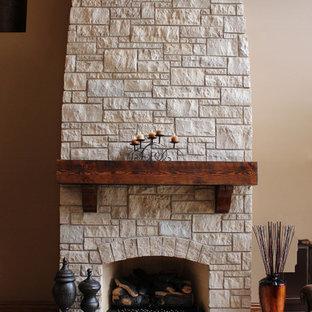 Idee per un grande soggiorno american style stile loft con pareti beige, pavimento in legno massello medio, camino classico, cornice del camino in pietra e nessuna TV