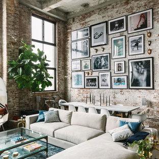 Foto de sala de estar abierta, industrial, con paredes rojas, suelo de cemento, suelo gris y televisor colgado en la pared