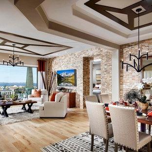Ispirazione per un ampio soggiorno stile americano aperto con parquet chiaro e TV a parete