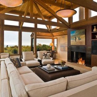 Diseño de sala de estar cerrada, costera, grande, con chimenea tradicional, pared multimedia, paredes beige, suelo de baldosas de porcelana y marco de chimenea de baldosas y/o azulejos