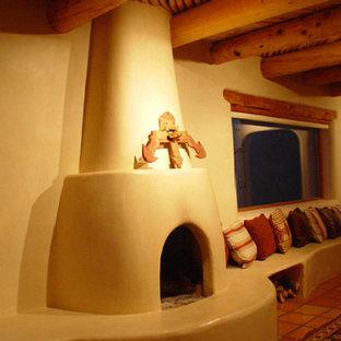 Idée de décoration pour une salle de séjour sud-ouest américain de taille moyenne et fermée avec un mur beige, un sol en carreau de terre cuite, une cheminée standard, un manteau de cheminée en plâtre, aucun téléviseur et un sol rouge.