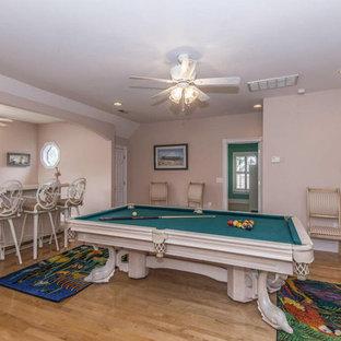 オーランドの大きいトロピカルスタイルのおしゃれな独立型ファミリールーム (ホームバー、ピンクの壁、淡色無垢フローリング、コーナー設置型暖炉、木材の暖炉まわり、据え置き型テレビ、茶色い床) の写真