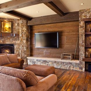 Inredning av ett rustikt mellanstort allrum med öppen planlösning, med en öppen hörnspis, en spiselkrans i sten, bruna väggar, mörkt trägolv, en väggmonterad TV och brunt golv