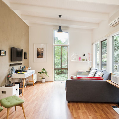 Example of a trendy medium tone wood floor family room design in Melbourne with white walls and a wall-mounted tv
