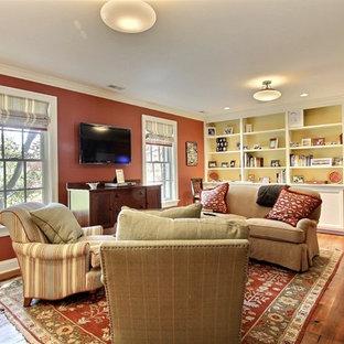 Klassisches Wohnzimmer mit oranger Wandfarbe, braunem Holzboden und Wand-TV in Baltimore
