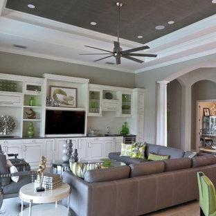 マイアミの大きいトロピカルスタイルのおしゃれなファミリールーム (グレーの壁、トラバーチンの床、暖炉なし、埋込式メディアウォール) の写真