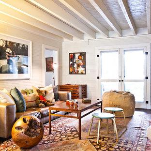Abgetrenntes Stilmix Wohnzimmer mit dunklem Holzboden und Eck-TV in Charleston