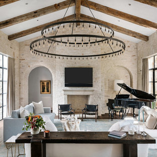 Family room - mediterranean dark wood floor family room idea in Austin with a music area, beige walls, a standard fireplace and a wall-mounted tv