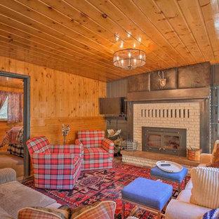 他の地域の中くらいのラスティックスタイルのおしゃれなオープンリビング (茶色い壁、淡色無垢フローリング、標準型暖炉、レンガの暖炉まわり、壁掛け型テレビ、グレーの床) の写真