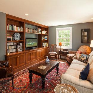 ボストンの小さいトラディショナルスタイルのおしゃれなファミリールーム (ライブラリー、グレーの壁、無垢フローリング、暖炉なし、据え置き型テレビ、茶色い床) の写真