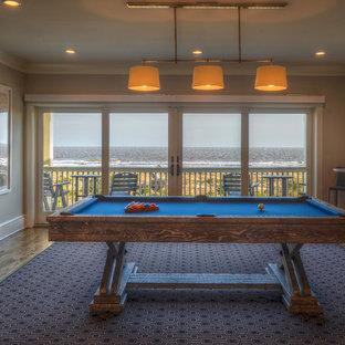 Aménagement d'une salle de séjour bord de mer de taille moyenne et fermée avec salle de jeu, un mur blanc, un sol en bois brun et un téléviseur fixé au mur.