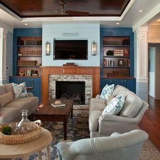 チャールストンの小さいトラディショナルスタイルのおしゃれなファミリールーム (無垢フローリング、標準型暖炉、レンガの暖炉まわり、壁掛け型テレビ、青い壁、茶色い床) の写真