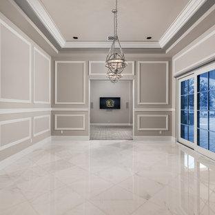フェニックスの巨大なラスティックスタイルのおしゃれなオープンリビング (ホームバー、マルチカラーの壁、大理石の床、標準型暖炉、石材の暖炉まわり、壁掛け型テレビ、マルチカラーの床) の写真