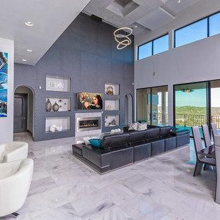 Modern inredning av ett mellanstort allrum med öppen planlösning, med blå väggar, marmorgolv, en standard öppen spis, en spiselkrans i metall, en väggmonterad TV och vitt golv