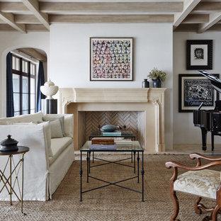 Modelo de sala de estar con rincón musical cerrada, mediterránea, grande, sin televisor, con paredes blancas, chimenea tradicional, suelo de piedra caliza, marco de chimenea de piedra y suelo beige