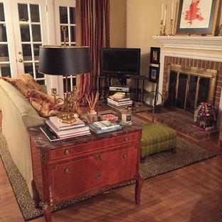 ローリーの中サイズのヴィクトリアン調のおしゃれなファミリールーム (ベージュの壁、無垢フローリング、標準型暖炉、レンガの暖炉まわり、据え置き型テレビ、茶色い床) の写真
