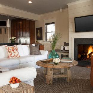 チャールストンの中くらいのビーチスタイルのおしゃれなオープンリビング (ベージュの壁、カーペット敷き、標準型暖炉、石材の暖炉まわり、壁掛け型テレビ) の写真