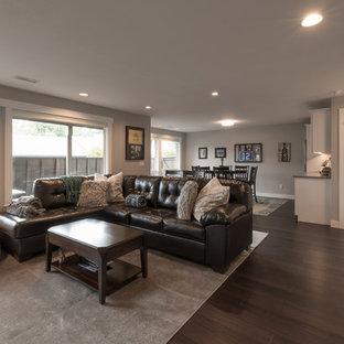 Diseño de sala de estar con barra de bar abierta, contemporánea, de tamaño medio, con paredes grises, suelo de madera oscura, chimenea tradicional, marco de chimenea de piedra, pared multimedia y suelo marrón
