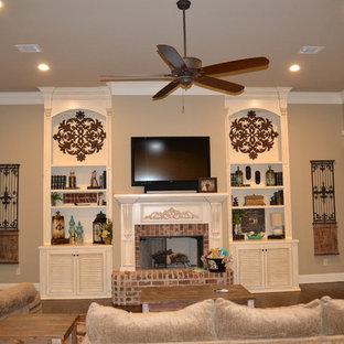 ニューオリンズの広い地中海スタイルのおしゃれな独立型ファミリールーム (濃色無垢フローリング、標準型暖炉、レンガの暖炉まわり、ベージュの壁、据え置き型テレビ、茶色い床) の写真