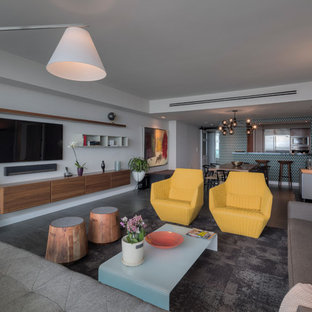 inspiration for an open concept black floor family room remodel in miami with white walls and