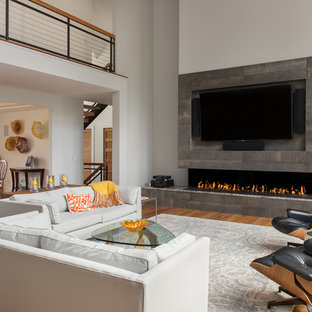 Large trendy open concept light wood floor and beige floor family room photo in Boston with gray walls, a ribbon fireplace, a tile fireplace and a concealed tv