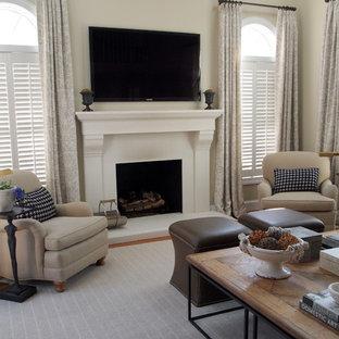 Imagen de sala de estar tradicional con paredes beige, chimenea tradicional y televisor colgado en la pared