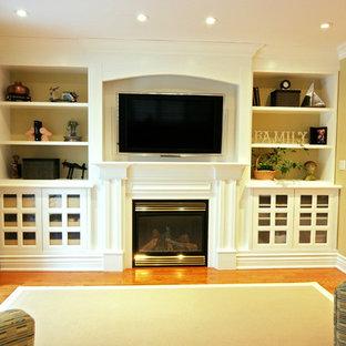 Réalisation d'une salle de séjour tradition de taille moyenne avec une cheminée standard, un manteau de cheminée en bois, un mur jaune, un sol en bois clair et un téléviseur encastré.