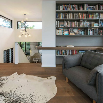 Trendy loft-style medium tone wood floor and brown floor family room library photo in Brisbane with white walls