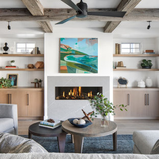 Inspiration for a large nautical open plan family and games room in Orange County with white walls, light hardwood flooring, a ribbon fireplace, a stone fireplace surround, no tv and beige floors.