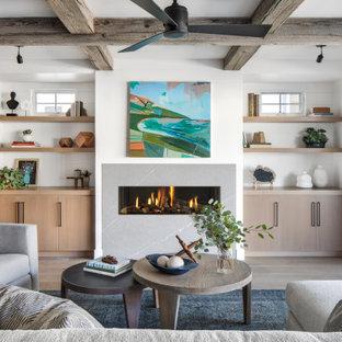オレンジカウンティの広いビーチスタイルのおしゃれなオープンリビング (白い壁、淡色無垢フローリング、横長型暖炉、石材の暖炉まわり、テレビなし、ベージュの床) の写真