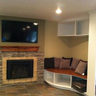 Esempio di un piccolo soggiorno chic chiuso con libreria, pareti beige, pavimento in ardesia, camino classico, cornice del camino in pietra e TV a parete