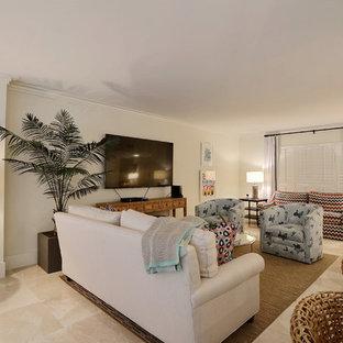 Imagen de sala de estar abierta, marinera, pequeña, con paredes blancas, suelo de baldosas de porcelana, televisor colgado en la pared y suelo beige