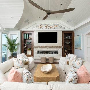 他の地域のビーチスタイルのおしゃれなファミリールーム (青い壁、横長型暖炉、石材の暖炉まわり、壁掛け型テレビ) の写真