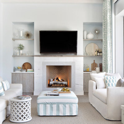 Family room - coastal enclosed family room idea in Miami with white walls, a standard fireplace and a wall-mounted tv
