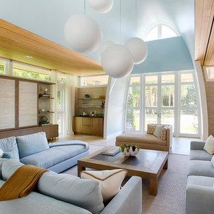 マイアミの大きいコンテンポラリースタイルのおしゃれなファミリールーム (内蔵型テレビ、青い壁、暖炉なし、茶色い床、ラミネートの床) の写真