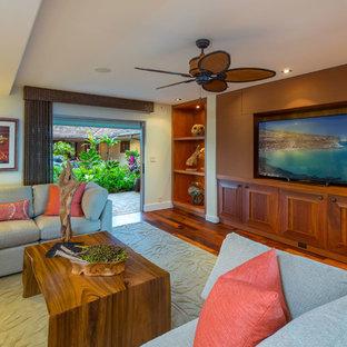 Immagine di un soggiorno tropicale con pareti gialle, pavimento in legno massello medio, TV a parete e pavimento arancione