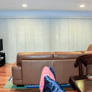 シンシナティの中サイズのコンテンポラリースタイルのおしゃれなファミリールーム (青い壁、無垢フローリング、標準型暖炉、レンガの暖炉まわり、据え置き型テレビ、茶色い床) の写真